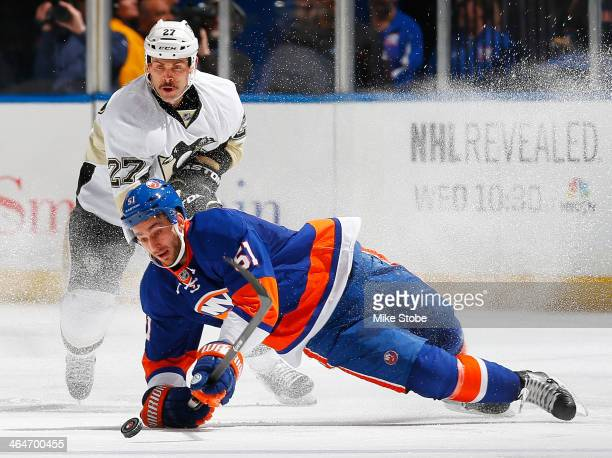 Frans Nielsen of the New York Islanders is tripped up in front of Craig Adams of the Pittsburgh Penguins at Nassau Veterans Memorial Coliseum on...