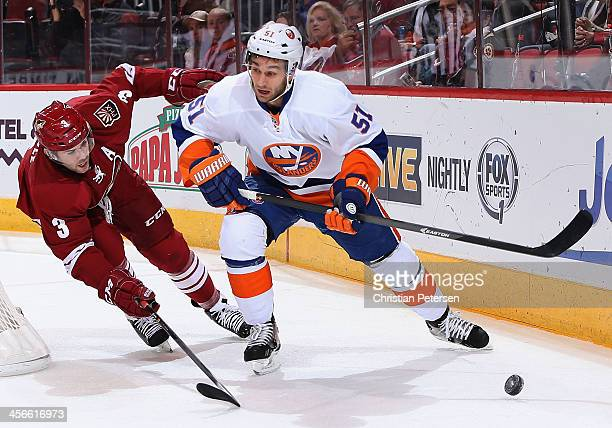 Frans Nielsen of the New York Islanders looks to pass the puck defended by Keith Yandle of the Phoenix Coyotes during the NHL game at Jobingcom Arena...