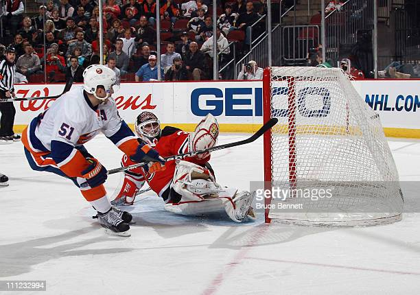 Frans Nielsen of the New York Islanders scores a third period goal against Martin Brodeur of the New Jersey Devils at the Prudential Center on March...