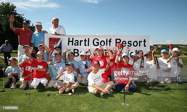 Franz Beckenbauer Bernhard Langer and Boris Becker pose with children during the opening of Hartl Golf resort on June 17 2007 in Penning Germany