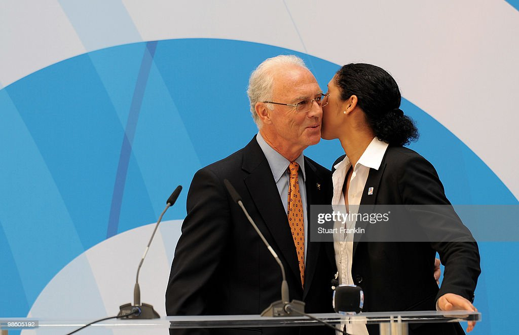 Franz Beckenbauer, chairman of the FIFA U20 and U17 Women's World Cup Committee is kissed by Steffi Jones, chairman of the Local Organising Committee during the FIFA U20 Women's World Cup draw on April 22, 2010 in Dresden, Germany.