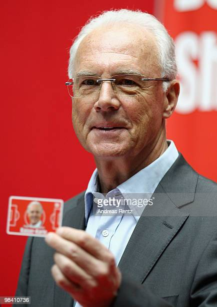 Franz Beckenbauer holds up the 'Franz Beckenbauers KaiserKarte' at a news conference during his visit to Axel Springer publishing house on April 12...