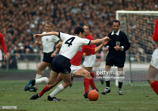 Franz Beckenbauer of West Germany moves past Bobby Charlton of England watched by referee Gottfried Dienst during the FIFA World Cup Final between...