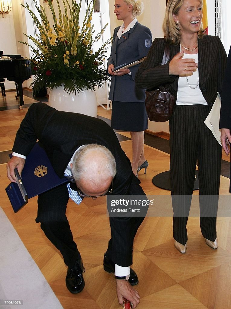 Franz Beckenbauer picks up his Federal Cross Of Merit after it fell from it's case at Bellevue Castle on October 4, 2006 in Berlin, Germany. German football legend Beckenbauer received the accolade for his life-long work as an international football player, national team coach and also for his engagement as president of the World Cup 2006 organizing committee.