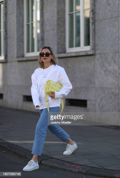 Franzi König wearing Acne Studios sweater, Bottega Veneta yellow leather bag, Levis jeans and white Reebok sneaker on February 28, 2021 in Cologne,...