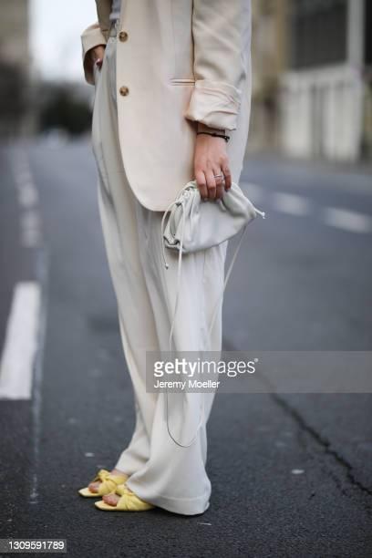 Franzi König wearing beige Zara suit and yellow heels and Bottega Veneta mini pouch bag on March 27, 2021 in Cologne, Germany.
