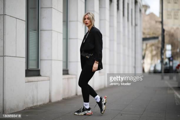 Franzi König wearing black Arket blazer, black Les Lunes leggings, white H&M top, Balenciaga triple S sneakers and black Jacquemus leather bag on...