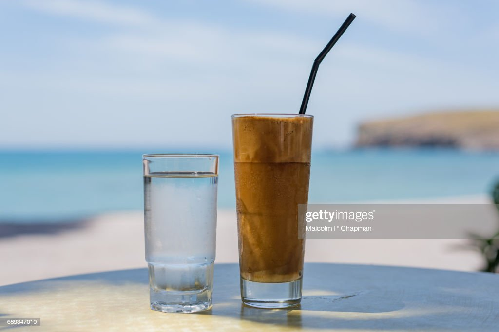 Frappe coffee drink served with a glass of water, Lesvos, Greece. : Stock Photo