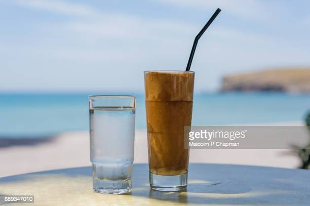 Frappe coffee drink served with a glass of water, Lesvos, Greece.