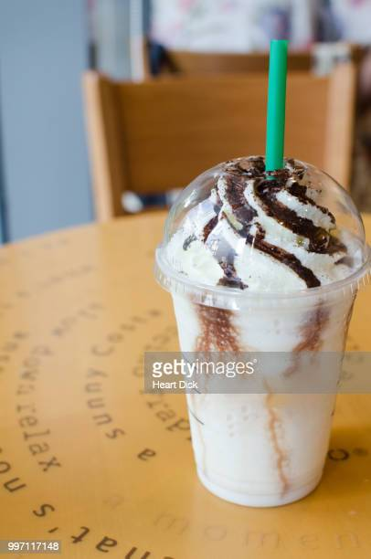 Frappe, milk, chocolate or coffee drink on brown wooden table.