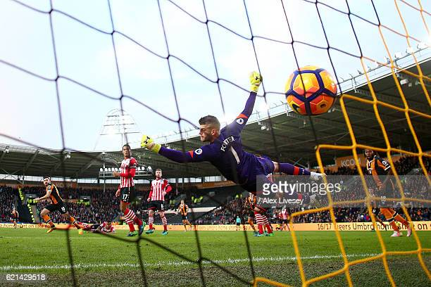 Fraser Forster of Southampton attempts to save as Robert Snodgrass of Hull City scores his sides first goal during the Premier League match between...