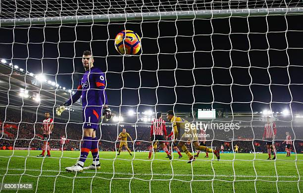 Fraser Forster of Southampton looks dejected as Dele Alli of Tottenham Hotspur celebrates as he scores their first and equalising goal during the...