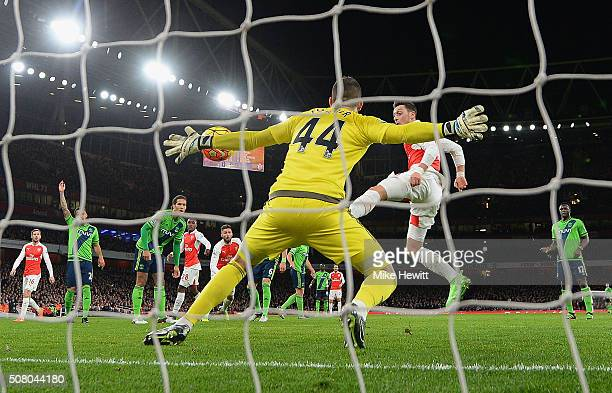 Fraser Forster of Southampton makes a save a shot by Mesut Ozil of Arsenal during the Barclays Premier League match between Arsenal and Southampton...