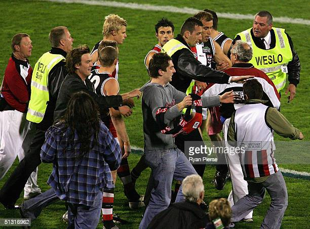 Fraser Gehrig for the Saints is escorted from the ground after kicking his 100th goal for the season during the AFL First Preliminary Final match...