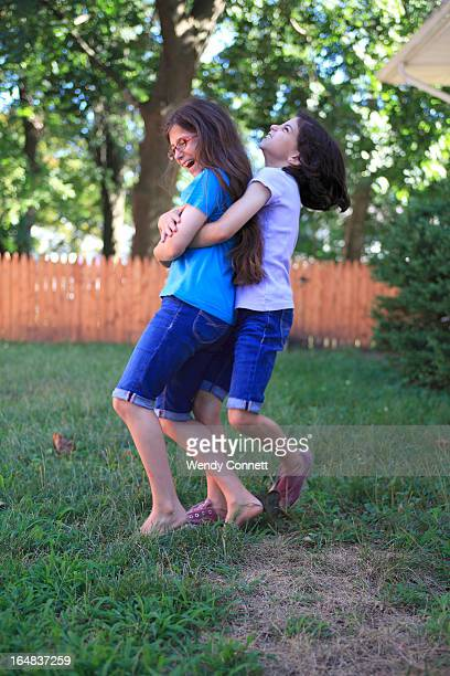 Fraternal Twin Sisters laughing, playing