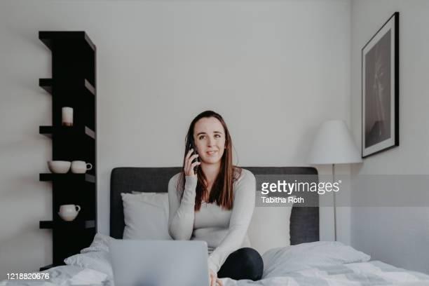 frau arbeitet von zu hause im home office im bett und telefoniert - frau fotografías e imágenes de stock
