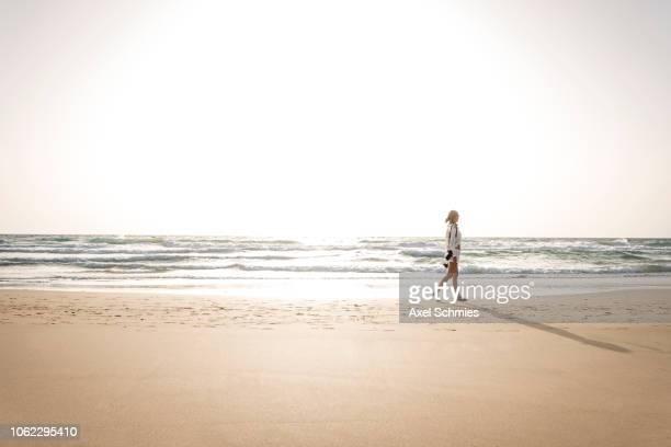 frau geht allein am sandstrand spazieren mit weißem outfit - frau fotografías e imágenes de stock