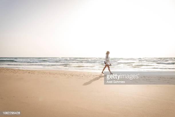 Frau geht allein am Sandstrand spazieren mit weißem Outfit
