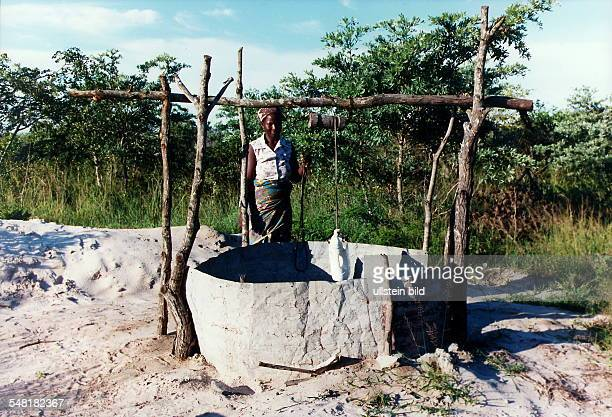 Frau holt Wasser an einem Ziehbrunnen Januar 1999
