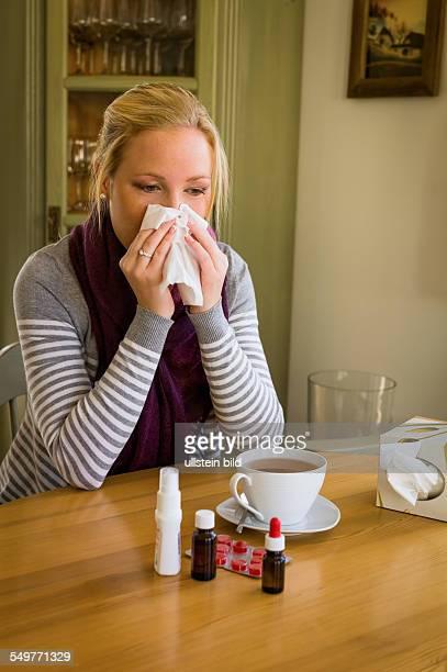 Frau im Krankenstand mit Taschentuch und Medikamenten Erkältung Schnupfen und Grippezeit