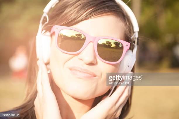 Frau im Sonnenlicht mit Kopfhörern und Sonnenbrille