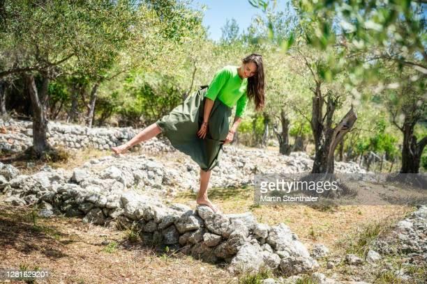 frau in grünem kleid in olivenhain auf steinen balancieren - kleid stock pictures, royalty-free photos & images