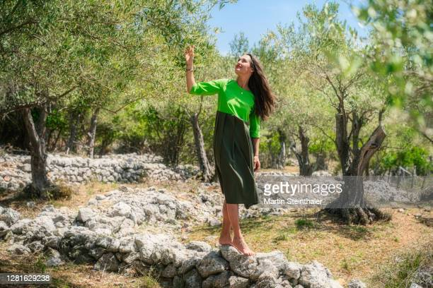 frau in grünem kleid in olivenhain auf steinen balancieren - frau photos et images de collection
