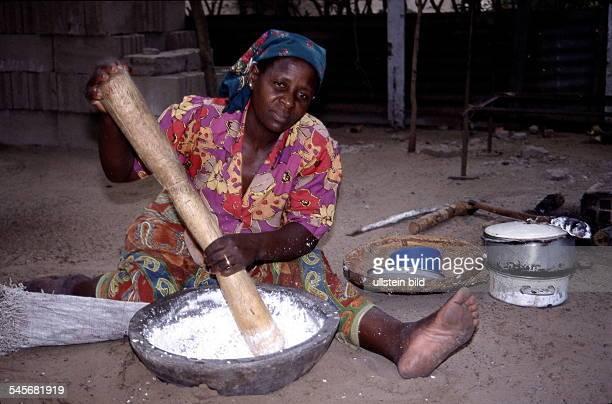 Frau in Maputo bei der Zubereitung von Essen / Mehl wird gestampft 1999