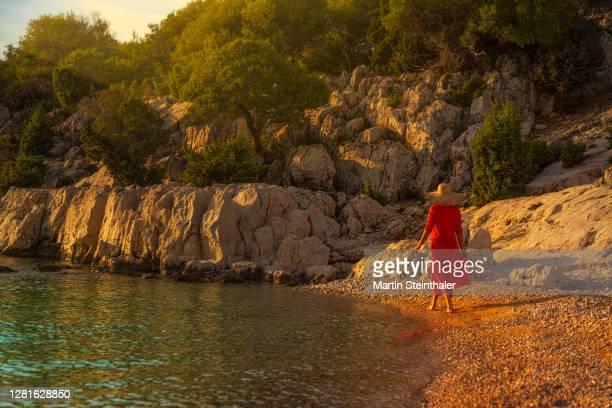 frau in rotem sommer - kleid spaziert am steinigen strand - kleid stock pictures, royalty-free photos & images