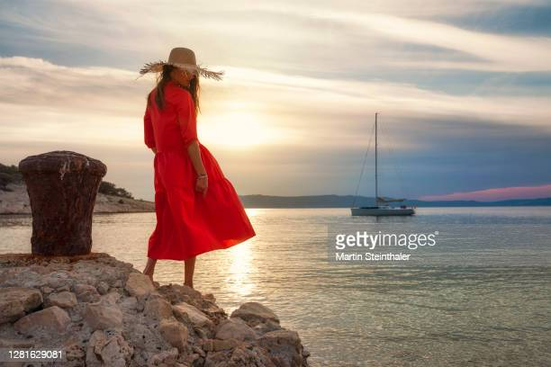 frau in rotem sommer - kleid steht am strand im abenddämmerung - kleid stock pictures, royalty-free photos & images