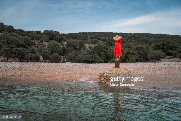 frau in rotem sommer - kleid steht auf felsen an steinigen strand - kleid stock pictures, royalty-free photos & images