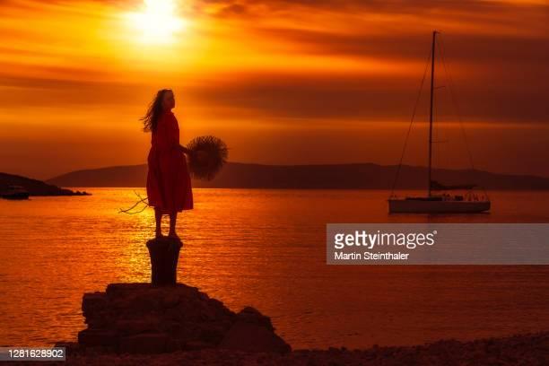 frau in rotem sommer - kleid steht auf felsen im sonnenuntergang - kleid stock pictures, royalty-free photos & images