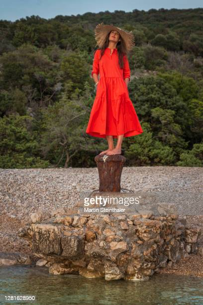 frau in rotem sommer - kleid steht auf felsen - frau photos et images de collection