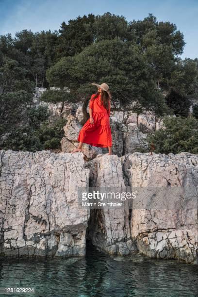 frau in rotem sommer - kleid steht auf felsen - kleid stock pictures, royalty-free photos & images