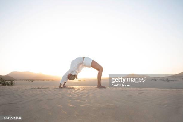 Frau in Yogapose Rad Brück auf sandigem Boden