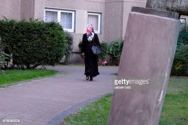 Frau mit einem Kopftuch auf dem Gehweg in BerlinWedding