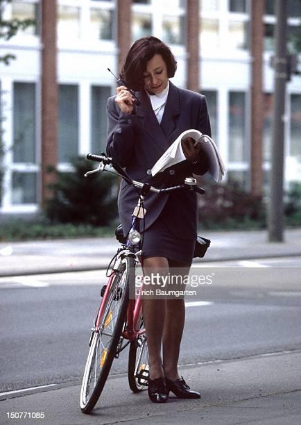 Frau mit Fahrrad und Mobiltelefon auf dem Weg ins Buero.