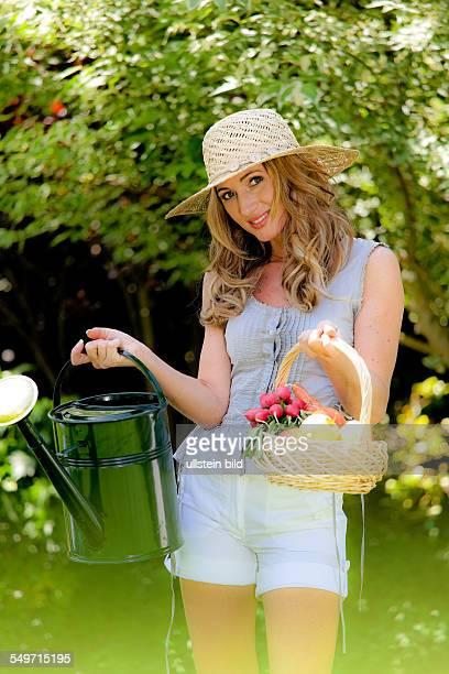 Frau mit Gießkanne und Korb mit Obst und Gemüse im Garten