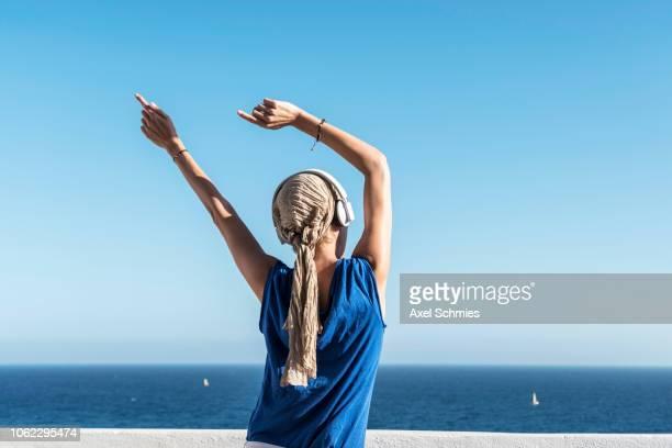 Frau mit Kopfhörer tanzt mit Armen in der Luft in der Sonne mit Blick aufs Meer