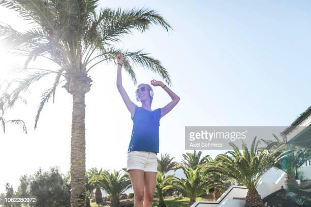 Frau mit Kopfhörer tanzt mit Armen in der Luft in der Sonne