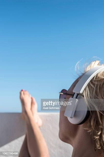 Frau mit Kopfhörer und hochgelegten Beinen auf Mauer in der Sonne