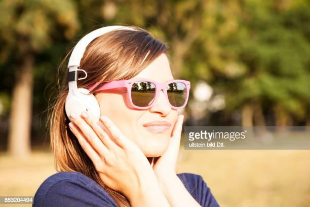 Frau mit Kopfhörern und Sonnenbrille im Park