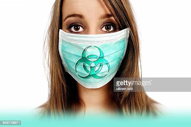 Frau mit Mundschutz und Biogefährdungszeichen, Symbolfoto Mers-Virus