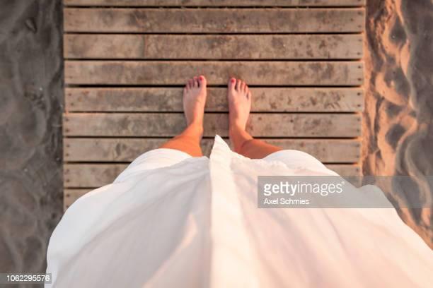 Frau mit weißer Bluse steht auf Steg im Sand, Blick nach unten