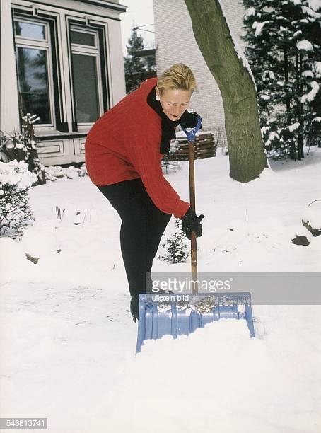 Frau räumt Weg zu ihrem Haus von Schnee frei. Aufgenommen Februar 1998.