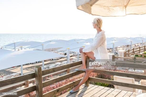 Frau sitzt auf Geländer einer Terrasse am Strand und blickt auf das Meer
