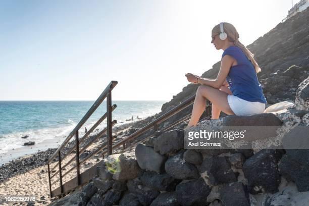 Frau sitzt auf Treppe am felsigen Strand mit Kopfhörer und hört Musik
