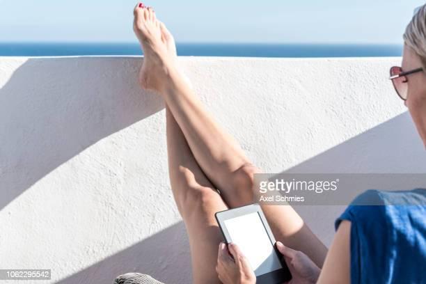 Frau sitzt in der Sonne mit hochgelegten Beinen auf Mauer und liest auf E-Reader