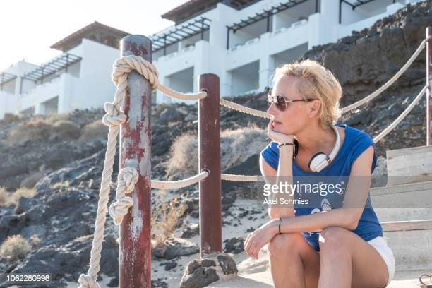 Frau sitzt nachdenklich mit Kopfhörer um den Hals auf einer Treppe am Strand