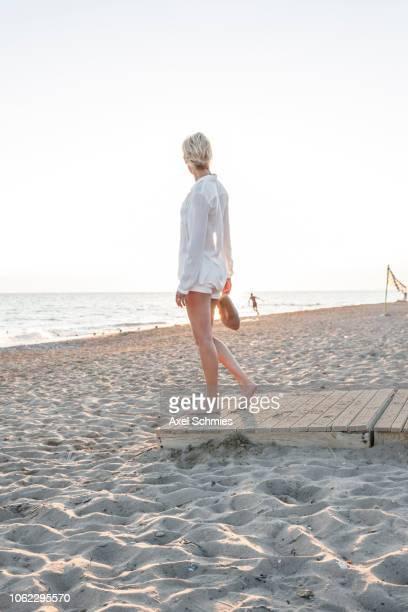 Frau steht auf Holzsteg im Sand und schaut auf das Meer